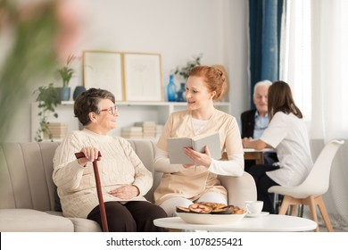 Professional caretaker in uniform reading a book to a happy senior woman with cane while sitting on a couch during leisure time in luxury nursing home common room with other people