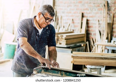 Professional carpenter cutting wooden board at his workshop