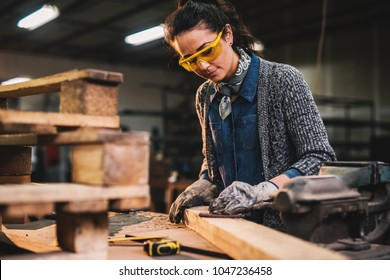 Professional carpenter woman sanding and preparing wood at the table in the fabric workshop.