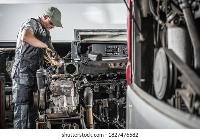 Professional Caucasian Automotive Mechanic in His 40s Repairing Powerful Heavy Duty Truck or Bus Diesel Engine Inside Truck Service Center. Transportation Industry Theme.