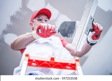 Professional Caucasian Construction and Remodeling Worker Preparing For Drywall Patching  Mixing Joint Compound While Staying on the Ladder.