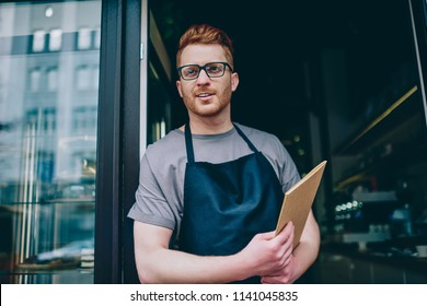 Professional caucasian waiter in black apron holding menu and smiling while inviting guests to own bakery shop.Positive male owner with red hair standing at entrance to cafeteria showing hospitality