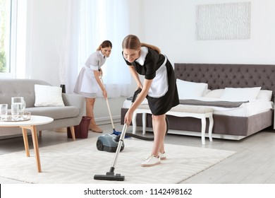 Professional chambermaids cleaning floor in hotel room