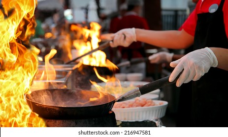 Professional Chef in a Commercial Kitchen Cooking Flambe. Two chefs cooking in outdoor kitchen. Chef frying food in flaming pan on gas hob in commercial kitchen.