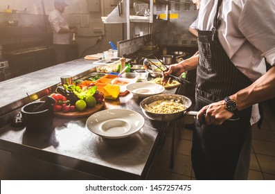 Professional chef cooking in the kitchen restaurant at the hotel, preparing dinner. A cook in an apron makes a salad of vegetables and pizza.