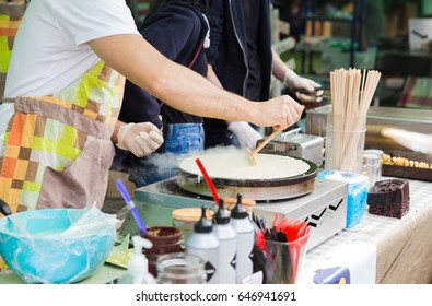 Professional chef cooking pancakes using batter spreader at the street food festival.