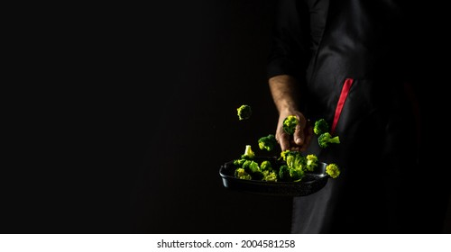Professional Chef Cooks Flambe Style. Hands of cook frying vegetables on pan. flying vegetables scattering in a freeze motion.