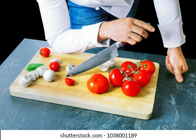 Professional chef cuts vegetables with a sharp knife from Damascus steel. Mixed media