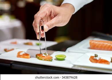 Professional chef decorating caper on sliced salmon