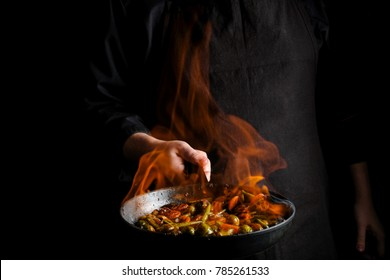Professional chef and fire. Cooking vegetables and food over an open fire on a dark background.
