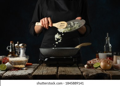 Professional chef pours chopped onion to pan wok. Backstage of cooking traditional Indian chicken curry on dark blue background. Concept of cooking tasty hot meal.