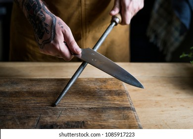 Professional chef sharpening knife in the kitchen