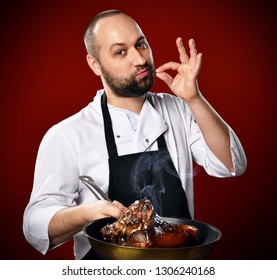 Professional chef shows sign Yummy and holds a frying pan with a just prepared meat on kitchen of the restaurant on red background.