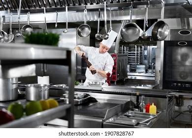 Professioneller Koch in weißen, gleichmäßigen Salzen Königsgarnelen. Holzsalzschleifer