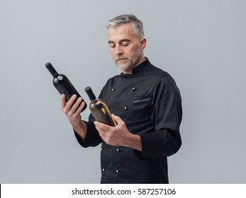 Professional chef and wine expert comparing wine bottles and reading labels, wine culture concept