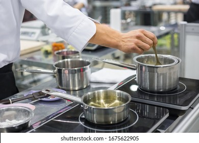 Professional chef workplace at cuisine of restaurant. Close up view of man hand stirring soup with spoon. Cooking, catering, culinary, gastronomy and food concept