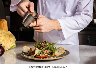 professional chef-cook gently pour the sauce on the salad in the kitchen. cropped man in apron make vegetarian salad dish for restaurant visitors