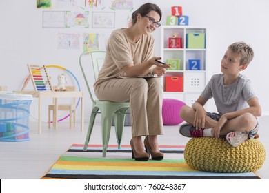 Professional child counselor during successful therapy session with little boy sitting on pouf in office room
