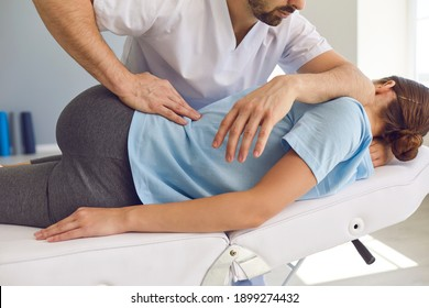 Professional chiropractor or physiotherapist helps to heal a young woman's back. Doctor fixes the patient lying on a couch of a modern rehabilitation clinic Concept of physical rehabilitation.