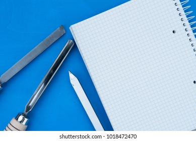 professional chisels with a paper notebook on a wooden blue background