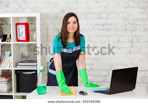 Professional cleaner cleans leans the house using a sponge and spray, standing in bright modern room