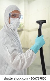 Professional cleaner in protective suit with safety goggles and mask about to commense work with his vacuum to clean the interior of a building