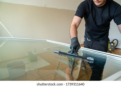 A professional cleaner using a squeegee and scraper to clean a large apartment window