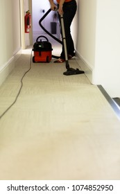 Professional cleaning service. Woman hoovering carpet in office. Low angle perspective vertical orientation