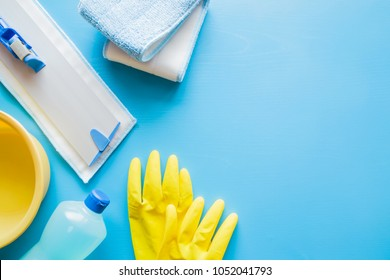 Professional cleaning set for different floor surfaces in kitchen, bathroom and other rooms. Empty place for text or logo on blue background. Cleaning service concept. Early spring regular clean up.