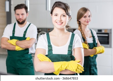 Professional cleaning team in uniforms and yellow rubber gloves