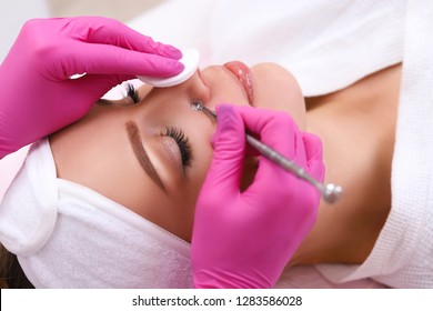 Professional cleansing of acne in a beauty salon.