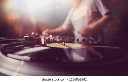 Professional club dj plays music set on party in night club.Retro turntables player device with vinyl record disc in closeup.Concert disc jockey mix msuical tracks on background.Vintage djs turn table