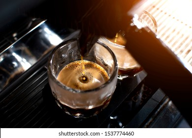 professional coffee machine makes double espresso in glasses, close-up of coffee preparation, drops fall in a cup