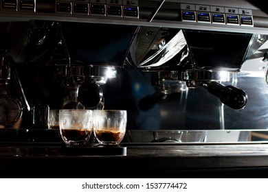 professional coffee machine makes double espresso in glasses at night, the process of making coffee