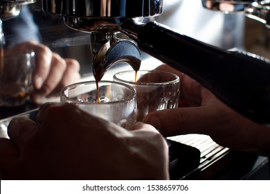 professional coffee machine makes double espresso in glasses at night, the process of making coffee, close-up