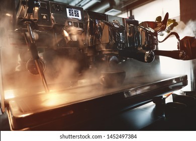 professional coffee machine in steam while barista making coffee drink whipping milk in pitcher with help of cappuccinator