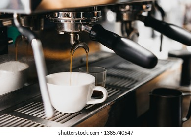 Professional coffee machine with white cup and pouring espresso. Coffee making process. Cappuccino feels a cup.