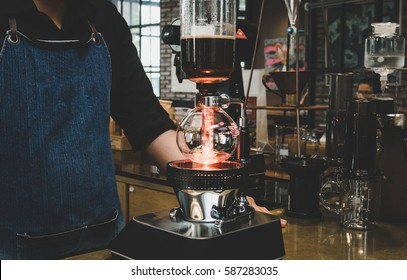 Professional coffee maker - Barista using coffee siphon brewing hot espresso at coffee shop
