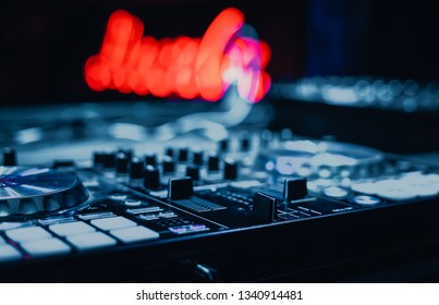 Professional concert dj setup on stage in bright blue neon lights.Djs midi controller for playing music on techno party.Disc jockey sound mixer deck to play & remix tracks on edm festival in nightclub