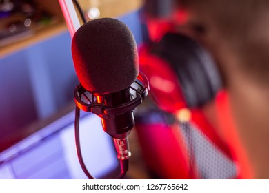 professional condenser microphone with windscreen mounted in an anti-vibration holder in front of the vocalist wearing headphones in the recording studio, backlit with red light, back view