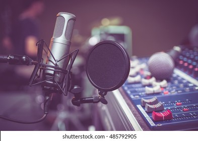 Professional condenser studio microphone over the musician blurred background and audio mixer, Musical instrument Concept