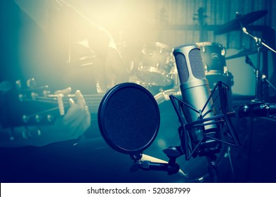 Professional condenser studio microphone over the Closeup musician playing the guitar on band background with spot light, Musical instrument Concept