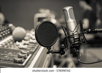 Professional Condenser Studio Microphone Over The Musician Blurred Background And Audio Mixer Musical Instrument Concept