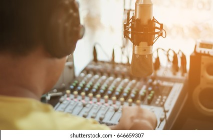 Professional condenser studio microphone over the abstract photo blurred of Hand adjusting audio mixer, Musical instrument Concept