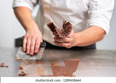 Professional confectioner making chocolate sweets at confectionery shop .