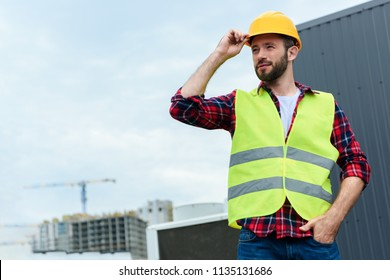 professional confident engineer in safety vest and helmet posing on roof