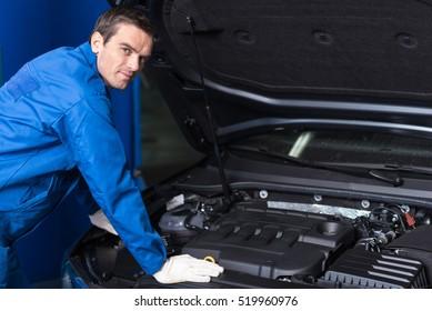 Professional confident mechanic chacking car engine