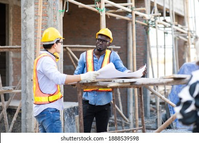 Professional Construction and  Engineer team Working on workplace. Professional black architect and construction worker working look at blueprint plan on site.