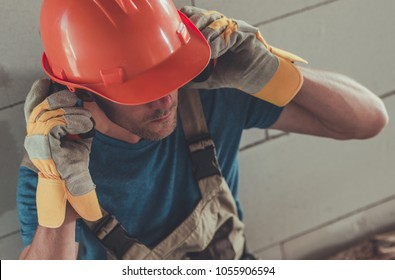 Professional Construction Protection Equipment. Caucasian Contractor Wearing Noise Reduction Headphones, Hard Hat and Protection Gloves.