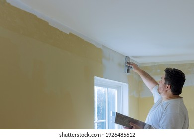 Professional construction worker applying plaster coating to the freshly plasterboard wall during room renovation